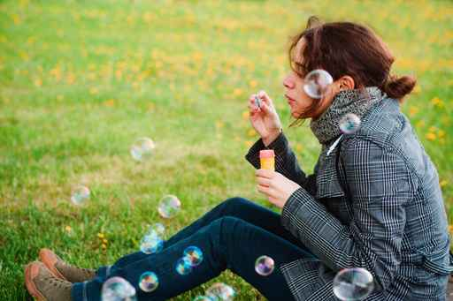 girl blow soap bubble against a background grass