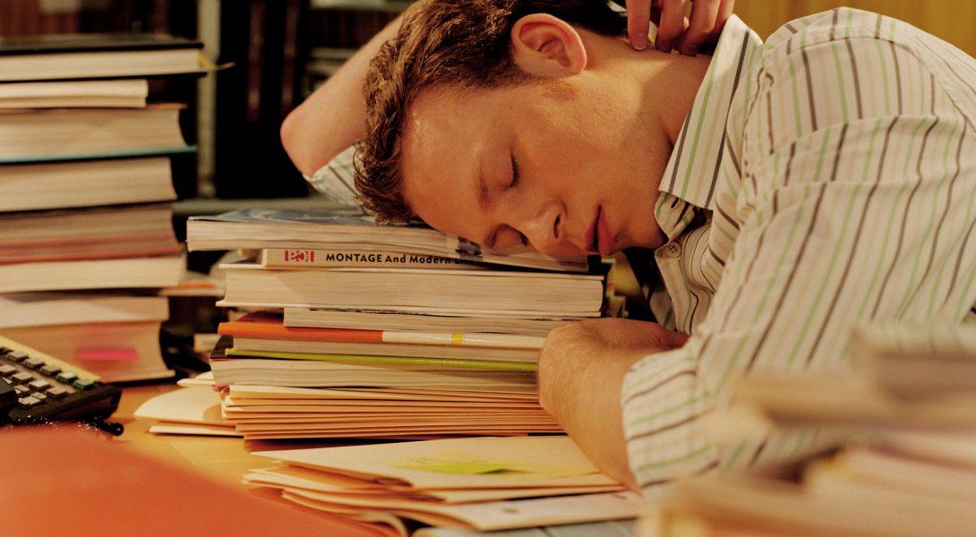 Man sleeping at desk, head resting on pile of books